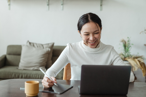 woman-on-laptop-smiling-while-taking-notes