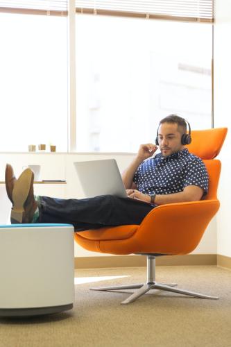 man-sitting-in-chair-wearing-headphones-using-laptop
